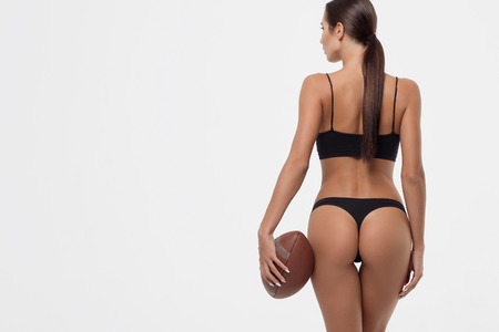 Back view of sexy young woman buttocks in lingerie holding rugby ball Imagens