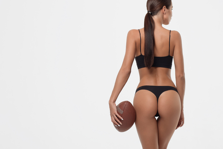 Back view of erotic young woman buttocks in lingerie holding rugby ball