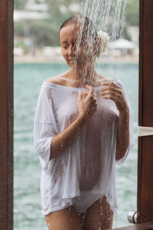 Crop woman in wet blouse avoiding water splash