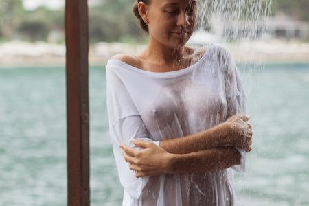 Mujer de cultivo en blusa mojada evitando salpicaduras de agua Foto de archivo