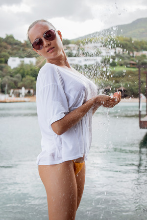 Attractive young female in wet blouse looking away while standing near splashing clean water in resort Banque d'images
