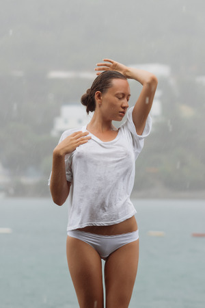 Attractive young female in while blouse and panties embracing herself and keeping eyes closed while standing near water on windy day Banco de Imagens