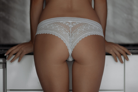 Back view of sensual female in lace panties touching soft buttocks while standing in stylish room
