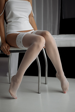 Girl in stockings sitting on a chair