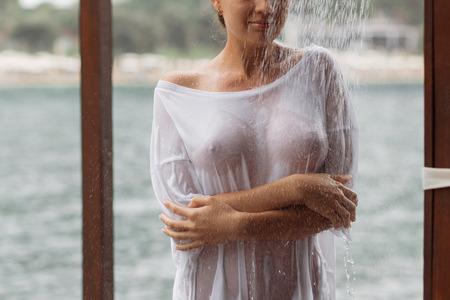 Atractiva mujer joven en blusa mojada mirando a otro lado mientras está de pie cerca de salpicaduras de agua limpia en el resort