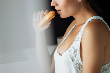 beautiful young girl in lingerie having breakfast with croissant in the kitchen Stock Photo