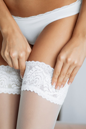 Close up photo of a slender beautiful woman corrects a garter on her leg Stock Photo