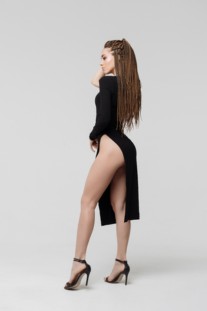 Side view of sensual young female with long dreadlocks wearing amazing black dress and looking at camera while standing on light gray background