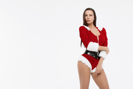 Surprised young woman in santa claus costume isolated on white