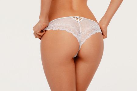 Female butt, white background. Beautiful female butt in a Thong.