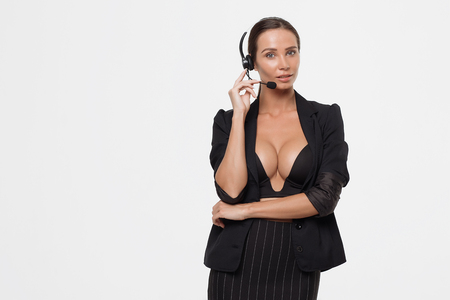 Isolated attractive sexy woman in black opened costume with hand on belt holding headphones micro and looking away