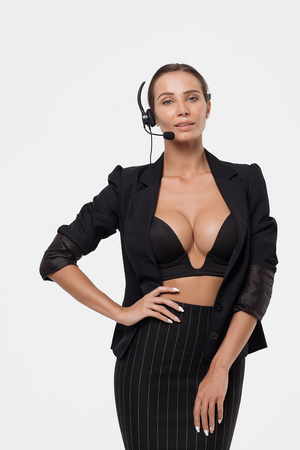 Isolated attractive woman in black costume with headphone, showing hand and another on belt looking away