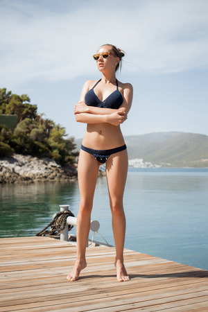 From below shot of attractive lady in knitted swimwear looking away while standing on yacht deck