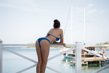 Side view of pretty young female in blue knitted bra looking away while leaning on railing on resort