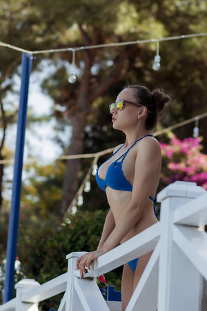 Sensual woman leaning on railing on resort Stock Photo