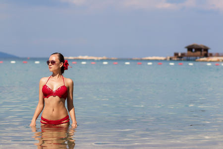 Lovely young lady in red knitted swimwear looking away and walking in sea water while relaxing in wonderful resort