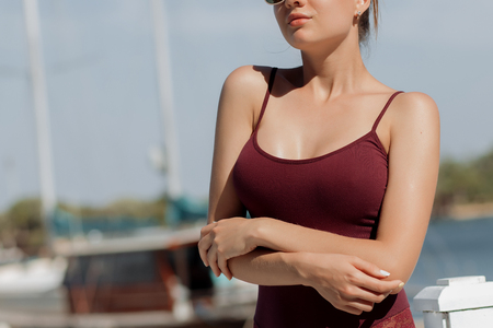 Sensual young female in lace swimwear looking away while leaning on railing on blurred background of resort Stock Photo