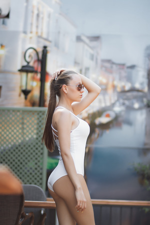 Attractive young lady in white swimsuit touching hair while standing near wooden column on resort