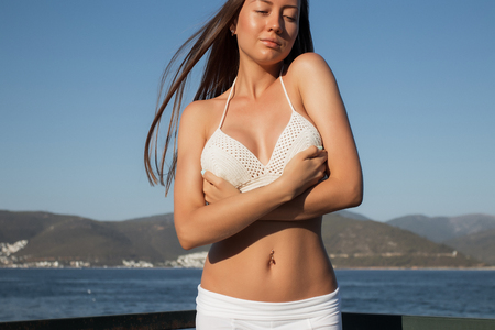 Side view of beautiful female in bra leaning on railing and admiring view of calm sea on sunny day on resort