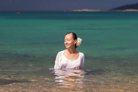 Sensual young female in wet blouse standing in clean sea water and looking away