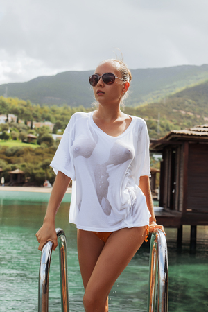 Attractive young woman in wet blouse standing on ladder and looking away near water on amazing resort 스톡 콘텐츠