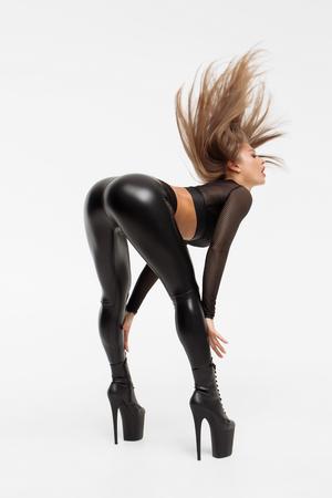 Séduisante femme portant des talons hauts avec un pantalon en cuir noir se penchant et posant de manière provocante