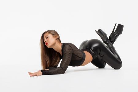 Attractive charming woman in leather suit and high heels on floor