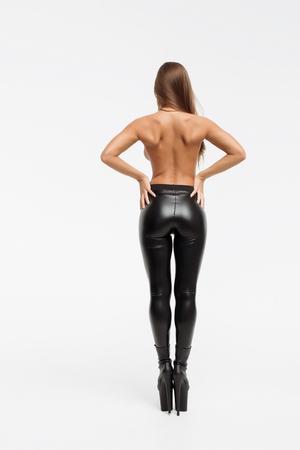 Schöne schlanke Frau in Lederhosen und High Hells, die sich mit den Händen schließen und die Kamera auf weißem Hintergrund betrachten