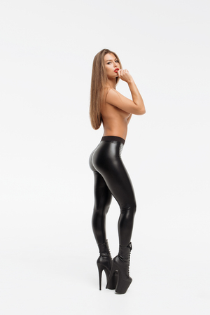 Attractive charming naked woman in leather trousers and high heels