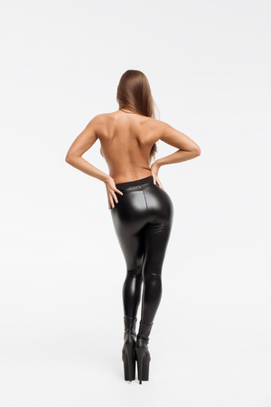 Beautiful slim woman in leather trousers and high hells closing by hands and looking at camera on white background