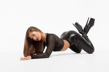 Side view of beautiful slim sexual woman in leather costume and high hells lying and looking at camera on white background