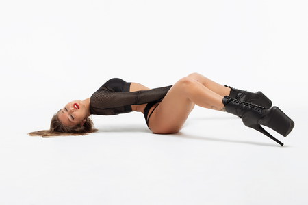 Side view of beautiful slim woman in underwear and high heels with upped legs lying and looking at camera on white background