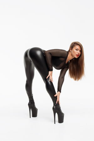 Alluring woman wearing high heels with black leather pants bending over and posing provocatively Stockfoto