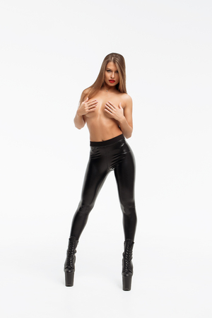 Beautiful slim sexual nude woman in leather trousers and high hells closing breast by hands and looking at camera on white background