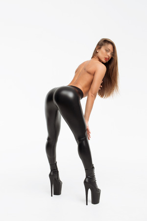 Alluring topless brunette in black leather pants and heels posing on white background