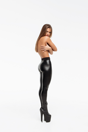 Beautiful slim woman in leather trousers and high hells closing breast by hands and looking at camera on white background Фото со стока
