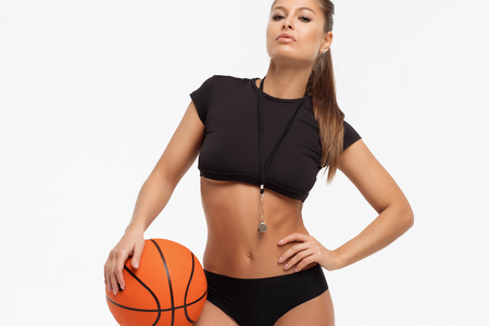 Beautiful slim sexual woman in underwear with whistle holding basketball ball and looking at camera on white background 版權商用圖片