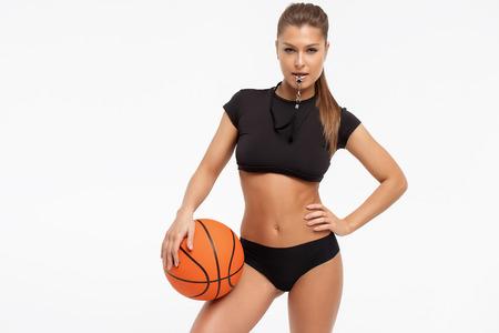 Schöne schlanke Frau in Unterwäsche mit Pfeife, die Basketballball hält und Kamera auf weißem Hintergrund betrachtet