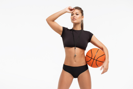 Beautiful slim woman in underwear with whistle holding basketball ball and looking at camera on white background