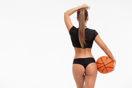 Back view of beautiful slim woman in underwear holding basketball ball and looking away on white background