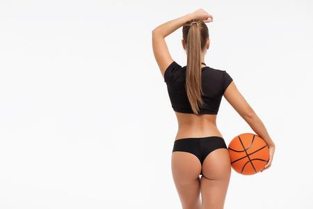 Vista posterior de la hermosa mujer delgada en ropa interior sosteniendo una pelota de baloncesto y mirando a otro lado sobre fondo blanco.