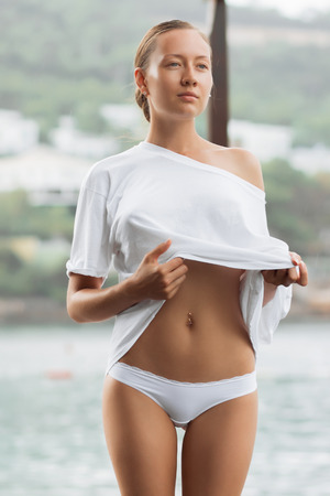 Attractive young female in while blouse and panties embracing herself and keeping eyes closed while standing near water on windy day Stok Fotoğraf