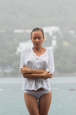 Attraktive junge Frau, während Bluse und Höschen sich umarmen und die Augen geschlossen halten, während sie an windigem Tag in der Nähe von Wasser stehen