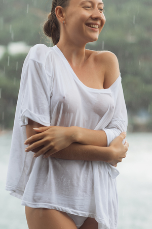 Attractive young female in while blouse and panties embracing herself and keeping eyes closed while standing near water on windy day
