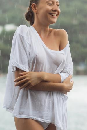 Attraente giovane femmina mentre camicetta e mutandine si abbracciano e tengono gli occhi chiusi mentre si trovava vicino all'acqua in una giornata ventosa