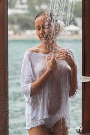 Attraktive junge Frau, während Bluse und Höschen sich umarmen und die Augen geschlossen halten, während sie an windigem Tag in der Nähe von Wasser stehen Standard-Bild