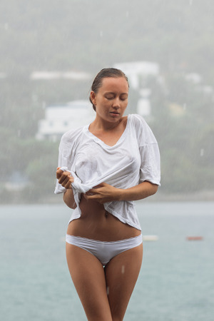 Attractive young female in while blouse and panties embracing herself and keeping eyes closed while standing near water on windy day Archivio Fotografico