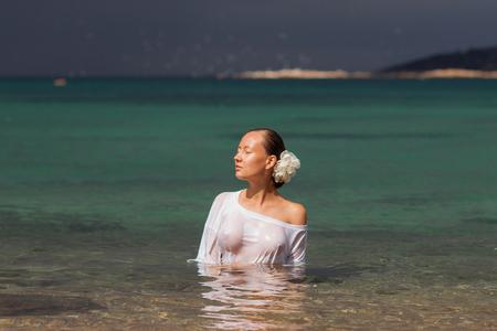 Sensuale giovane donna in camicetta bagnata in piedi in acqua di mare pulita e distogliere lo sguardo Archivio Fotografico