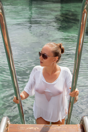 Attractive young woman in wet blouse standing on ladder and looking away near water on amazing resort