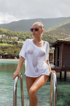 Mujer joven atractiva en blusa mojada de pie en la escalera y mirando a otro lado cerca del agua en un resort increíble